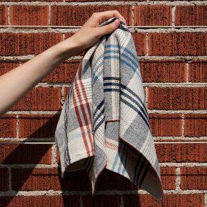 Hand holding a handwoven tea towel