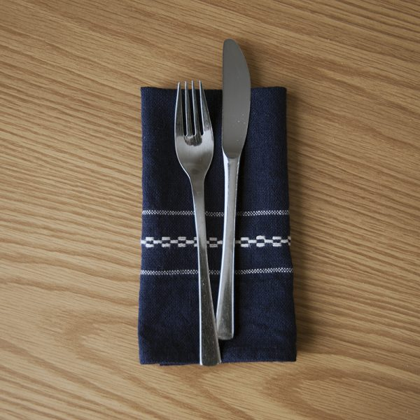 Image of woven napkin from Railroad Runners weaving pattern with a fork and knife on top