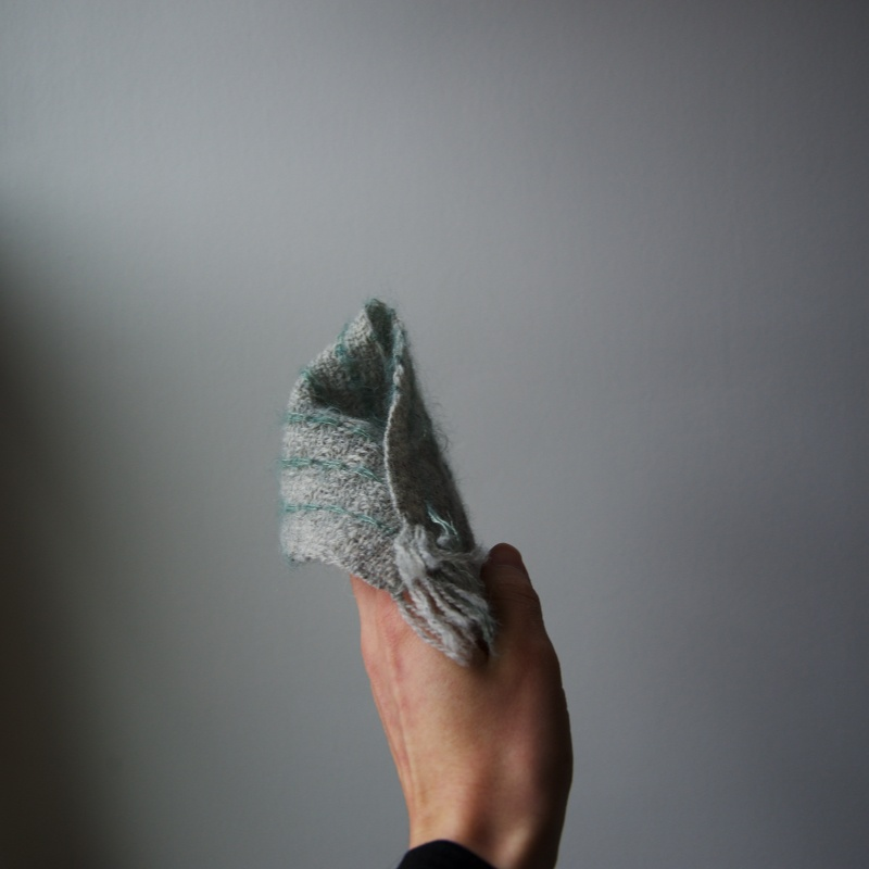 folded weaving sample in a hand