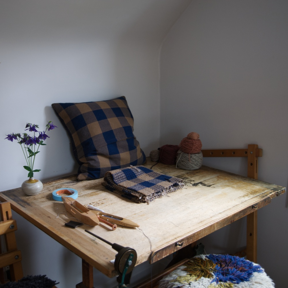 A desk with a cushion, weaving shuttles, and a flower vase